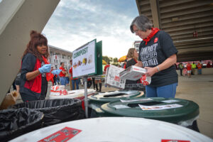 NC State University compost volunteer Lynn Odom puts pizza boxes in the proper composting bins during halftime of the Wolfpack football game against Clemson University in Raleigh, NC.